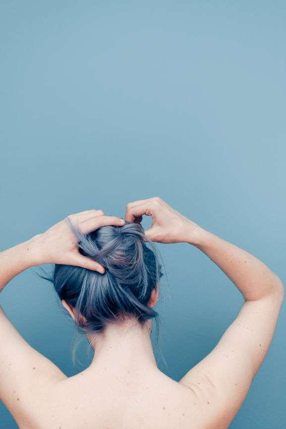 Frau mit grau gefärbtem Haar bindet sich Bun