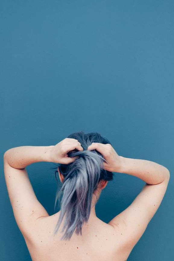 Frau mit grau gefärbtem Haar bindet sich Haargummi in Ponytail