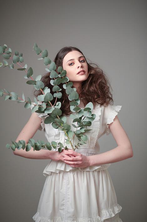Frau mit braunem Haar und Zweigen in der Hand